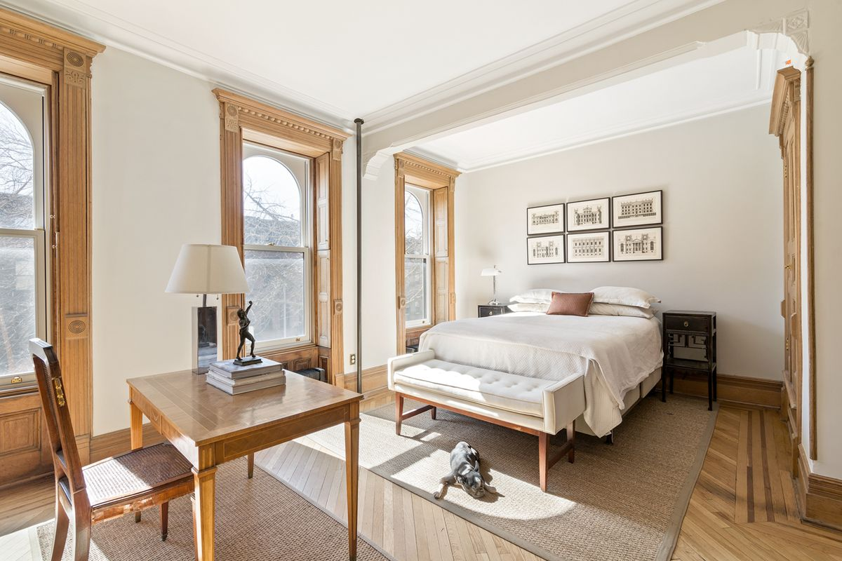 The master bedroom features three street-facing windows lined with pale oak boxes.