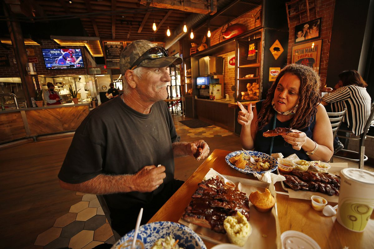 A couple sits indoors at a restaurant eating barbecue.