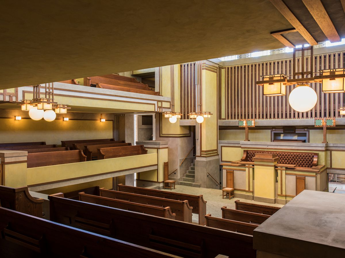 The interior of the Unity Temple. There are multiple benches and an altar with a musical organ.
