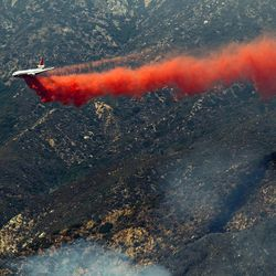 A DC-10 tanker drops fire retardant on a ridge line in the Angeles National Forest, Tuesday, Sept. 4, 2012 near Glendora, Calif. It could be a week before firefighters can contain this 3,600-acre blaze because of high temperatures and rugged terrain in thick brush that hasn't burned in a couple of decades.