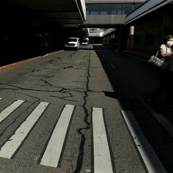 """A traveler walks to the parking lot at the Salt Lake City International Airport on Wednesday, April 8, 2020. Utah Gov. Gary Herbert announced new efforts on Wednesday """"to protect the people of Utah and slow the spread of coronavirus in the state"""" by closely monitoring its borders, as well as passengers who fly into the airport."""