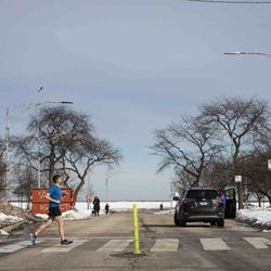 People walk and park on a portion West Lawrence Avenue east of Lake Shore Drive that had been closed since March amid fears of the coronavirus pandemic, Tuesday, Feb. 23, 2021. The Chicago Park District announced plans Tuesday to gradually reopen the city's lakefront, playgrounds and indoor swimming pools in response to sustained declines in COVID-19 positivity rates and cases.