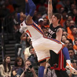 New York Knicks' Carmelo Anthony, left, is fouled by Miami Heat's Mike Miller in the first half of an NBA basketball game in New York, Sunday, April 15, 2012.