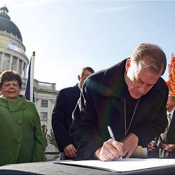 Bishop John C. Wester signs a document called the Utah Compact in support of immigration reform at the State Capitol in Salt Lake City Thursday.