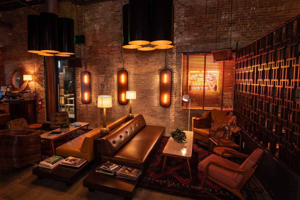 A restaurant with brick walls and midcentury lights.