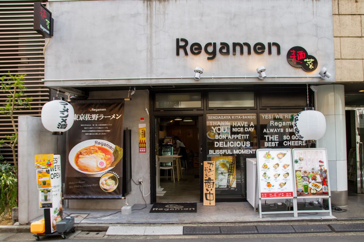 A restaurant exterior with bright photographs of food and text in both English and Japanese.