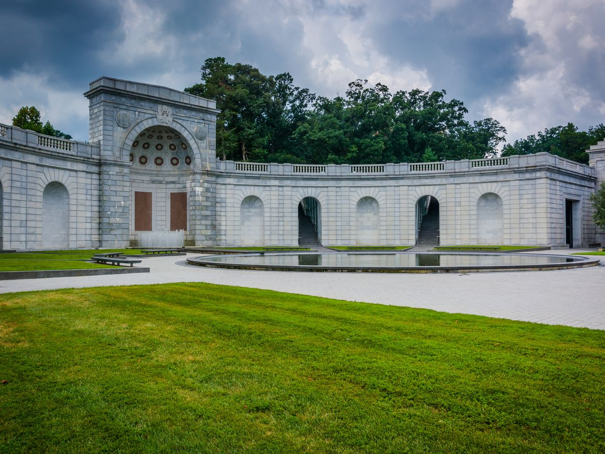 A war memorial for women who served in the U.S. Armed Forces. It is a wide architectural structure with a rounded alcove in the middle, and is surrounded by grass.