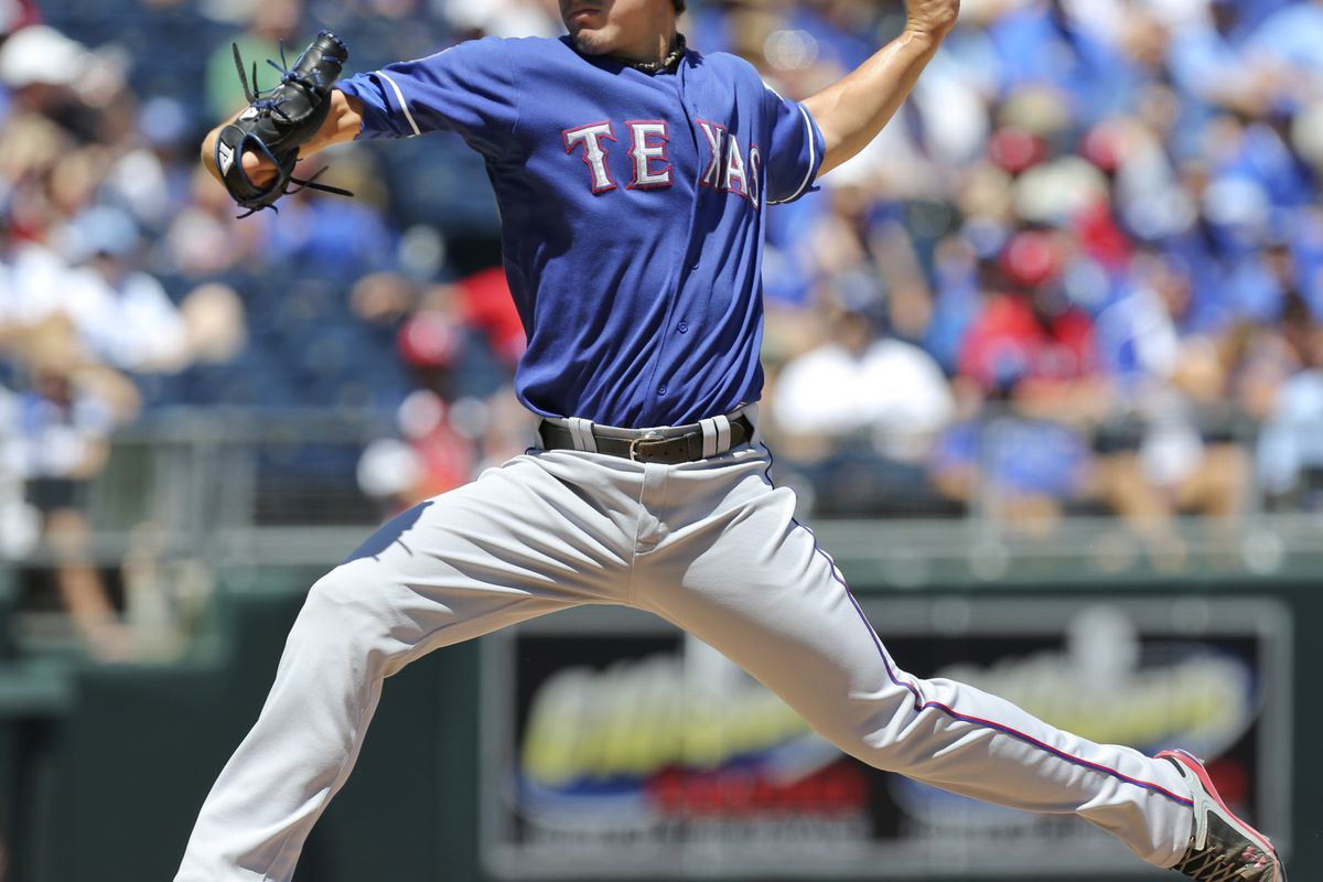KANSAS CITY, MO - AUGUST 05:  Derek Holland #45 of the Texas Rangers pitches against the Kansas City Royals in the first inning at Kauffman Stadium on August 5, 2012 in Kansas City, Missouri. (Photo by Ed Zurga/Getty Images)