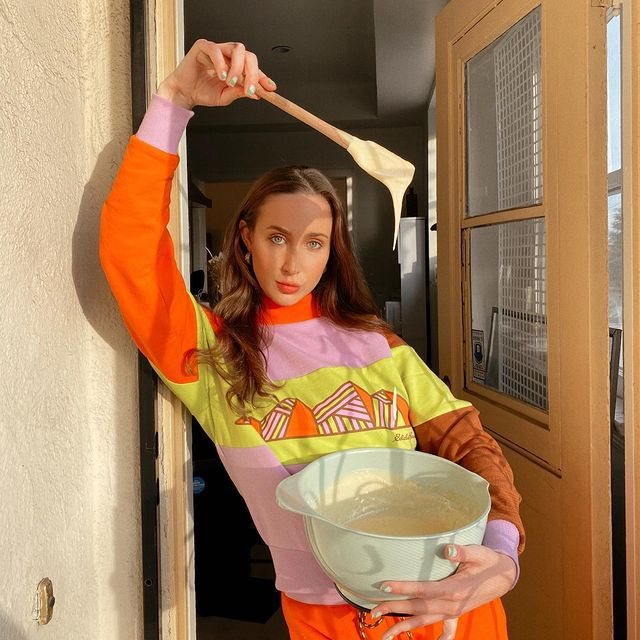 Thin white woman with long brown hair in a brightly-colored sweatshirt, leaning in a sunlit doorframe, holding a spatula dripping with batter over a large bowl