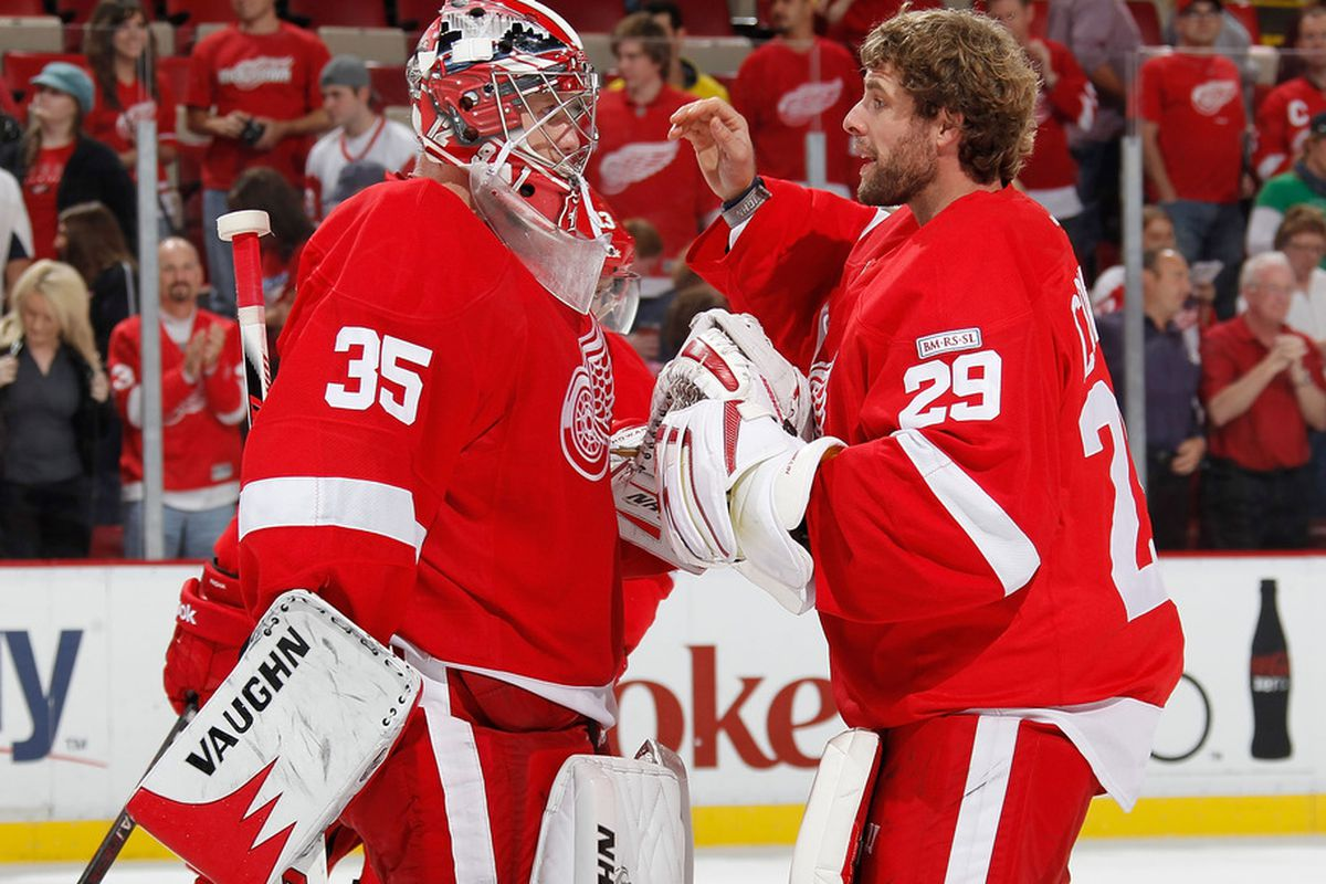 DETROIT, MI - OCTOBER 07: Jimmy Howard #35 of the Detroit Red Wings is congratulated after a 5-3 win over the Ottawa Senators by Ty Conklin #29  at Joe Louis Arena on October 7, 2011 in Detroit, Michigan.  (Photo by Gregory Shamus/Getty Images)