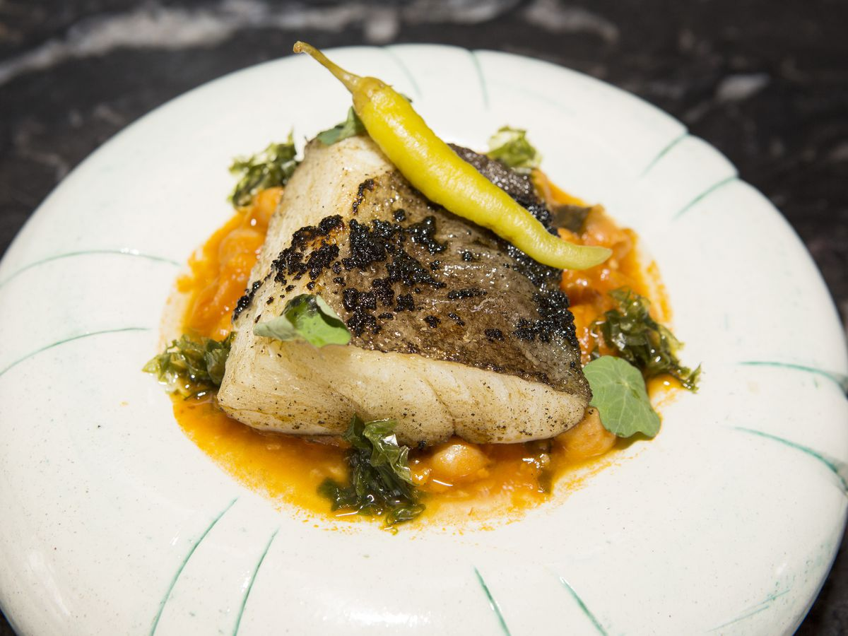 A fancy grilled filet of fish with sauce in a white bowl