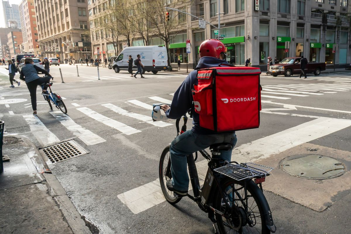 An image of a person riding a bike with a doordash red bag on the back