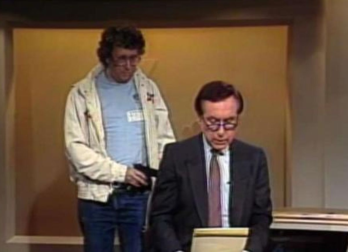 This Aug. 20, 1987, image made from video shows an intruder with a gun, as journalist David Horowitz is taken hostage during a live broadcast of Channel 4 Los Angeles. Horowitz remained calm and read the gunman's statements on camera. | NBC-TV via AP