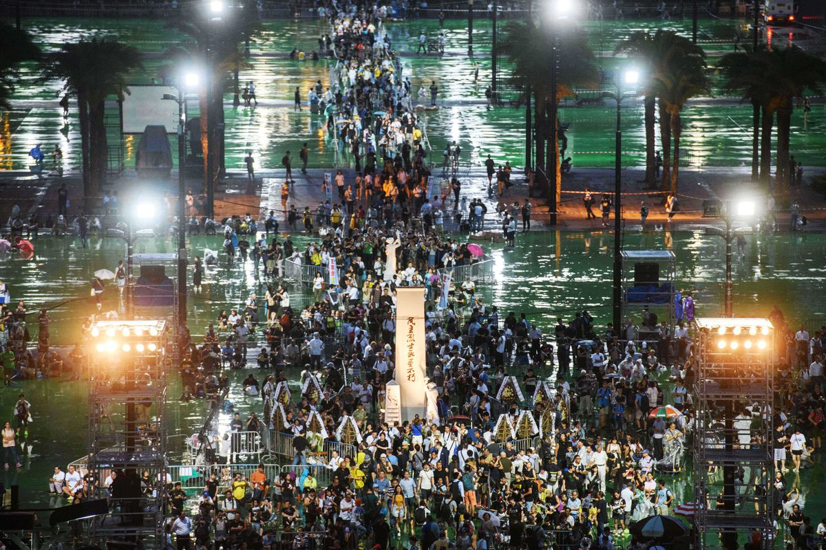 A large crowd gathers for a candlelight vigil at night in Hong Kong.