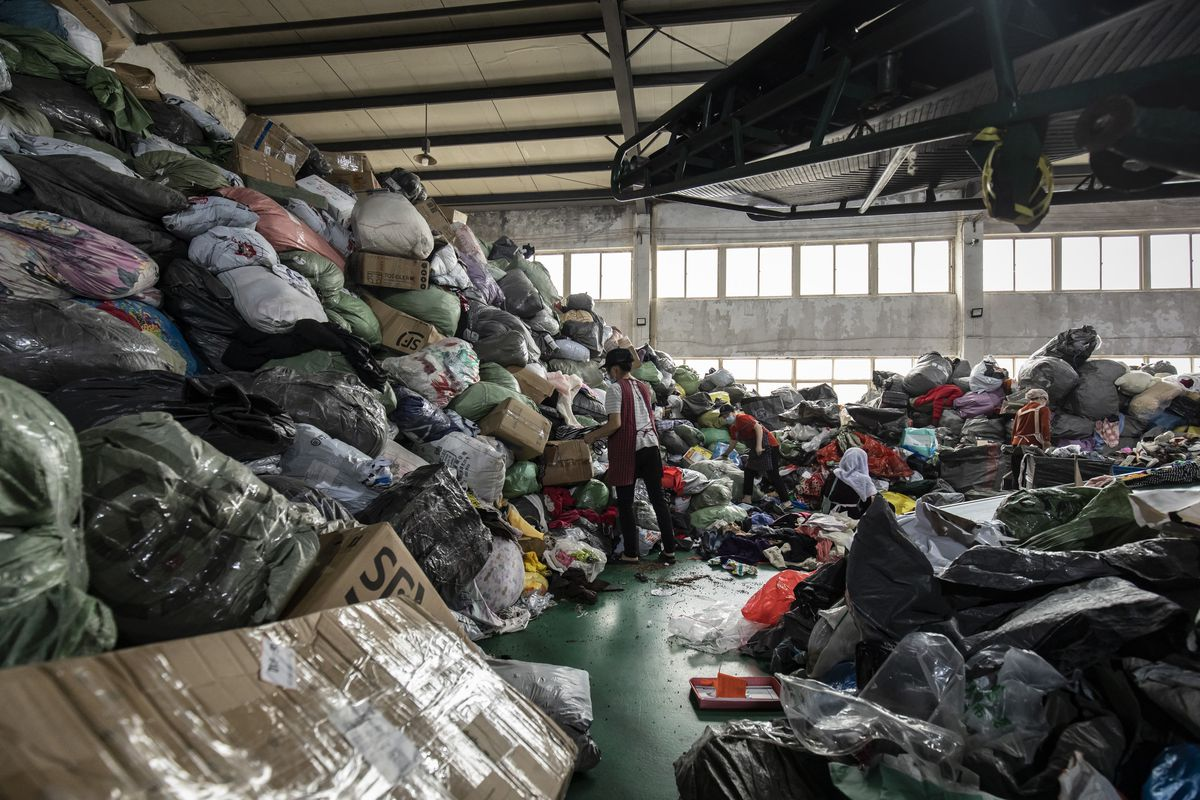 An employee sorts through bags of used clothing at a secondhand garment facility in Hangzhou, China.