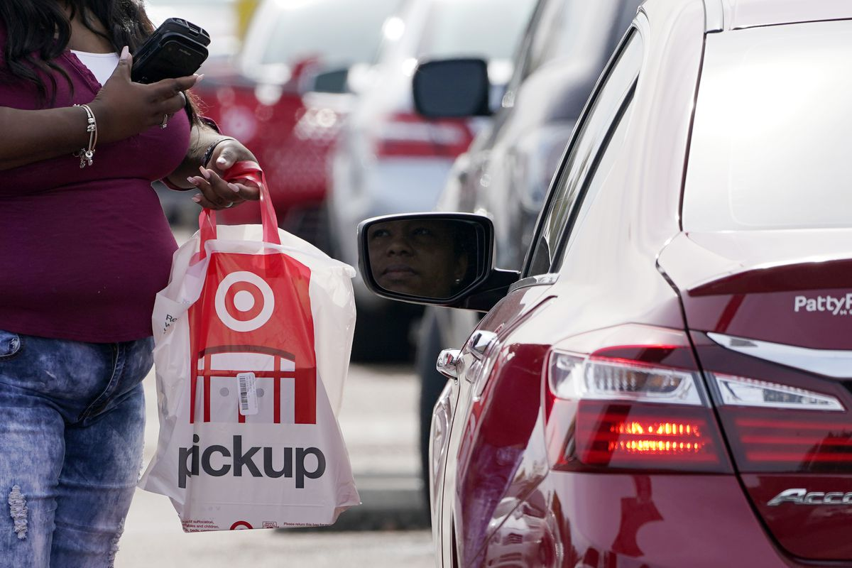 A Target employee prepares to hand a customer a curbside pickup purchase in Jackson, Miss., Thursday, Nov. 5, 2020.