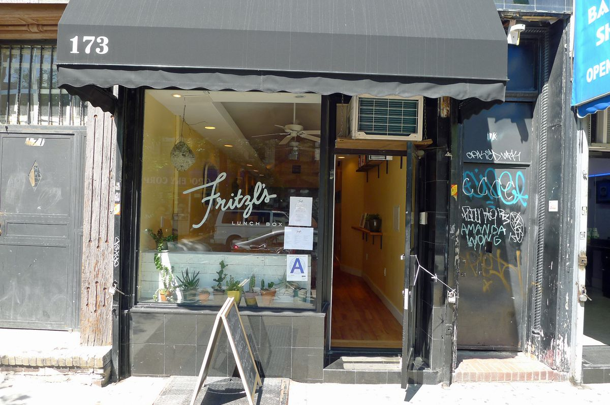 A narrow black storefront with Fritzl's in script on the window.