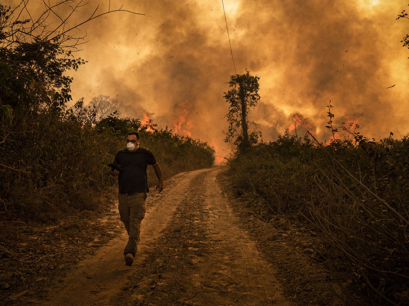A man wearing a face mask walks down a path away from fire and smoke behind him