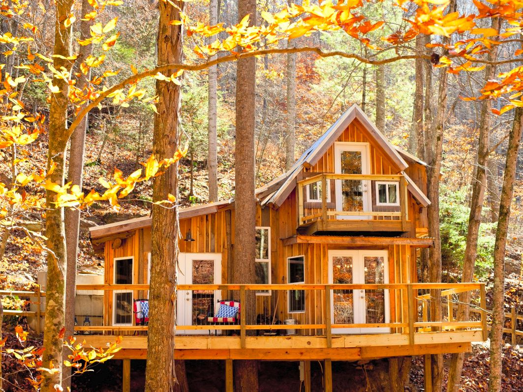 A wooden cabin with white-trimmed windows and a large wooden deck sits in a forest of yellow and golden trees.