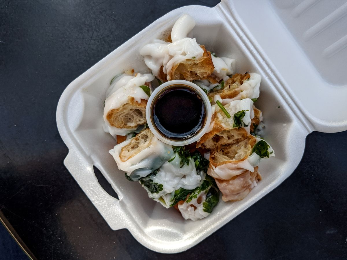 Overhead view of a white styrofoam container holding chunks of fried dough, each wrapped in a wide rice noodle, with a cup of soy sauce.