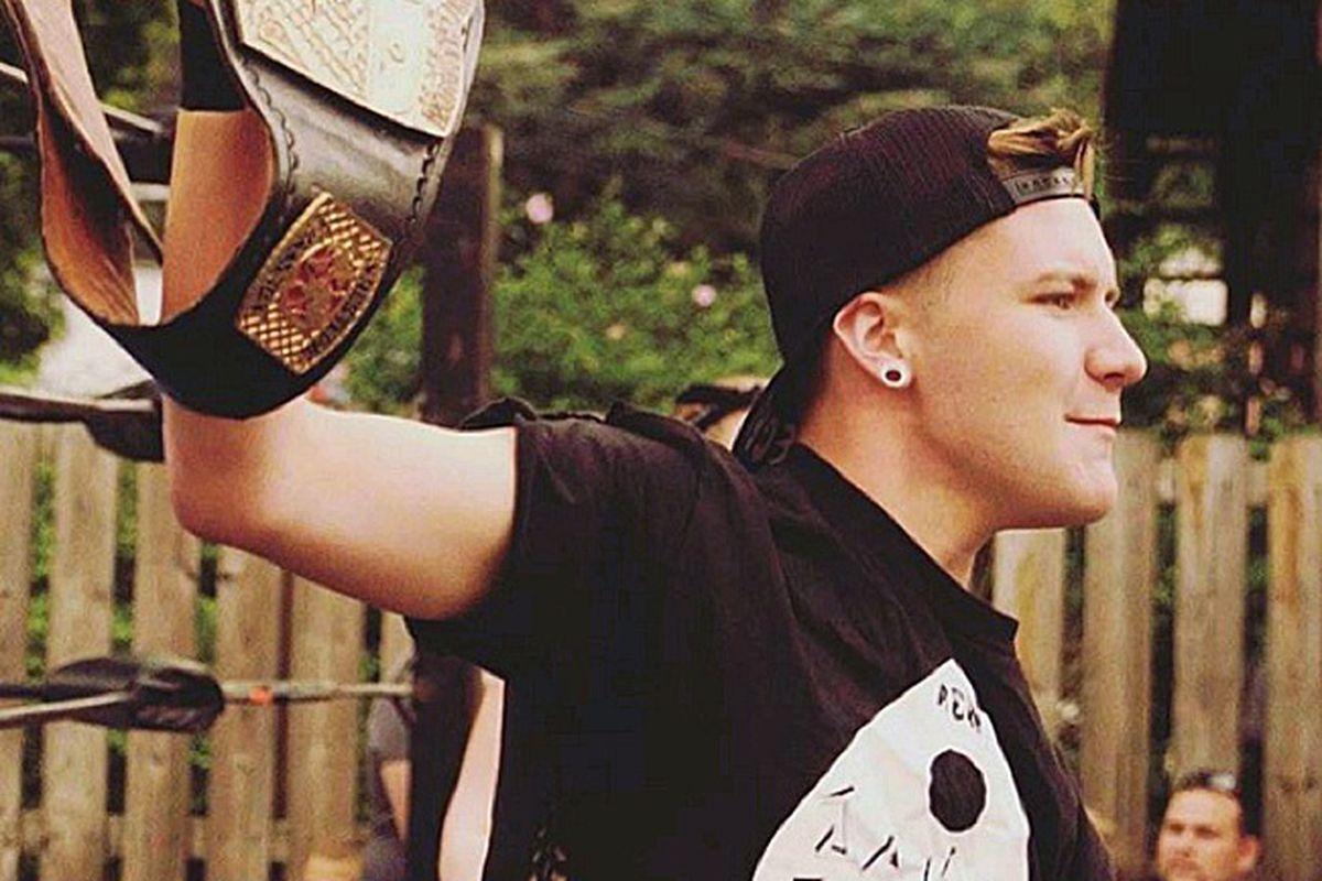 Jamie Senegal raises a wrestling title belt.