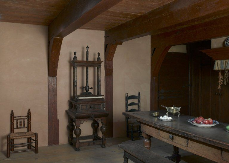 The interior of a historic house. There is a dining table with chairs and other kitchenware along the wall. There are exposed wooden beams on the ceiling and walls.