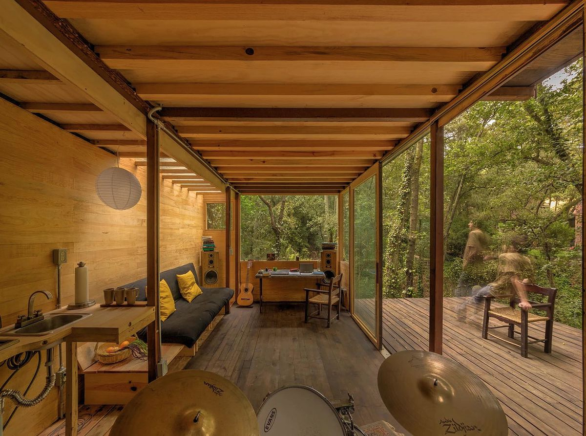 A living area in a treehouse. There is a drum set, couch, desk, chairs, and floor to ceiling windows overlooking trees.