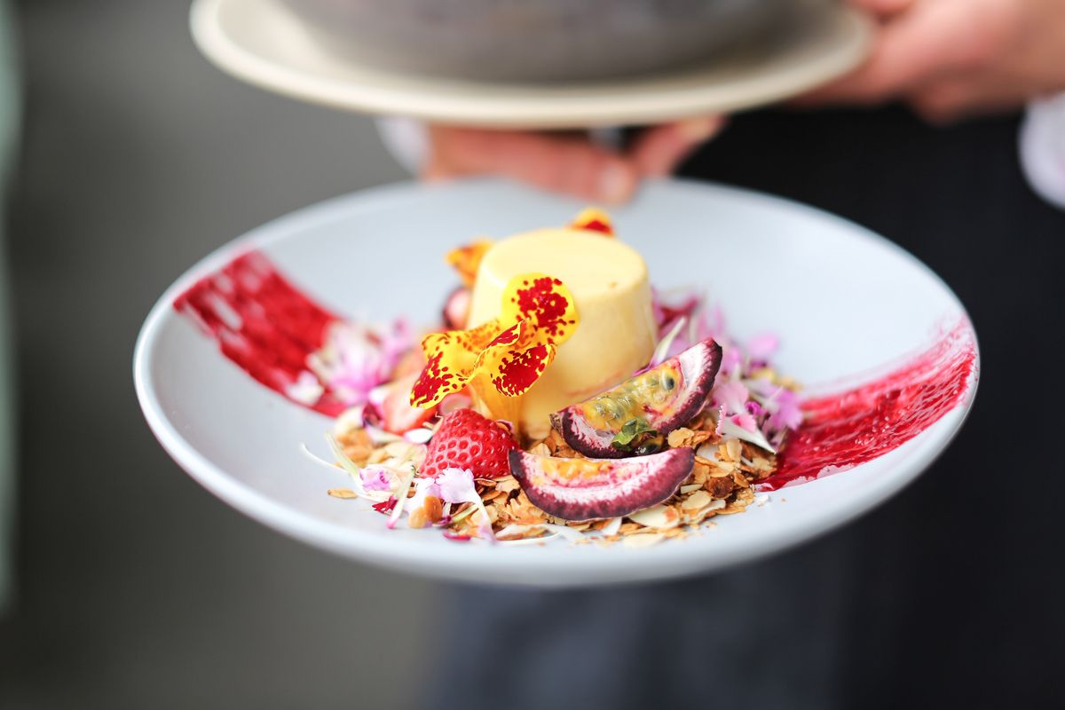 A server holds a white plate with panna cotta garnished with fruit, flowers, and nuts