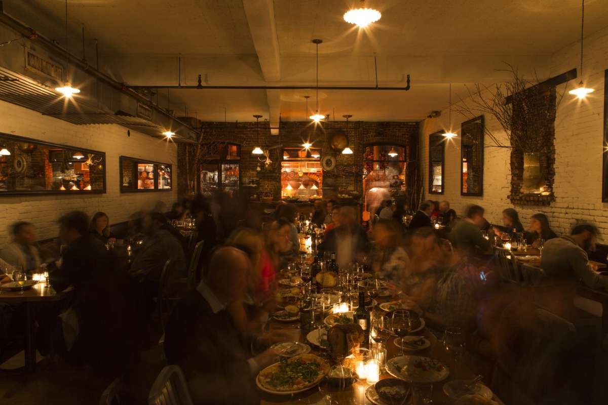 A dimly light restaurant with several people gathered around a central table, eating and talking.