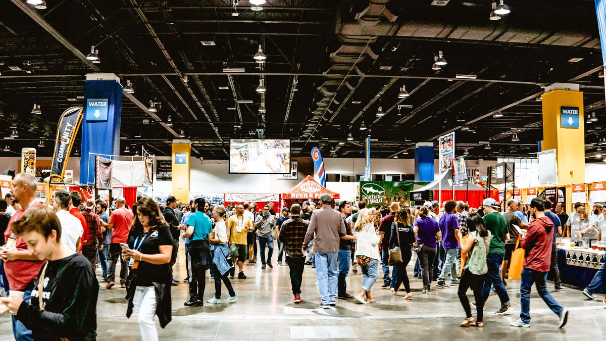 A wide shot of dozens of people walking through the Great American Beer festival with breweries lining the side of the shot