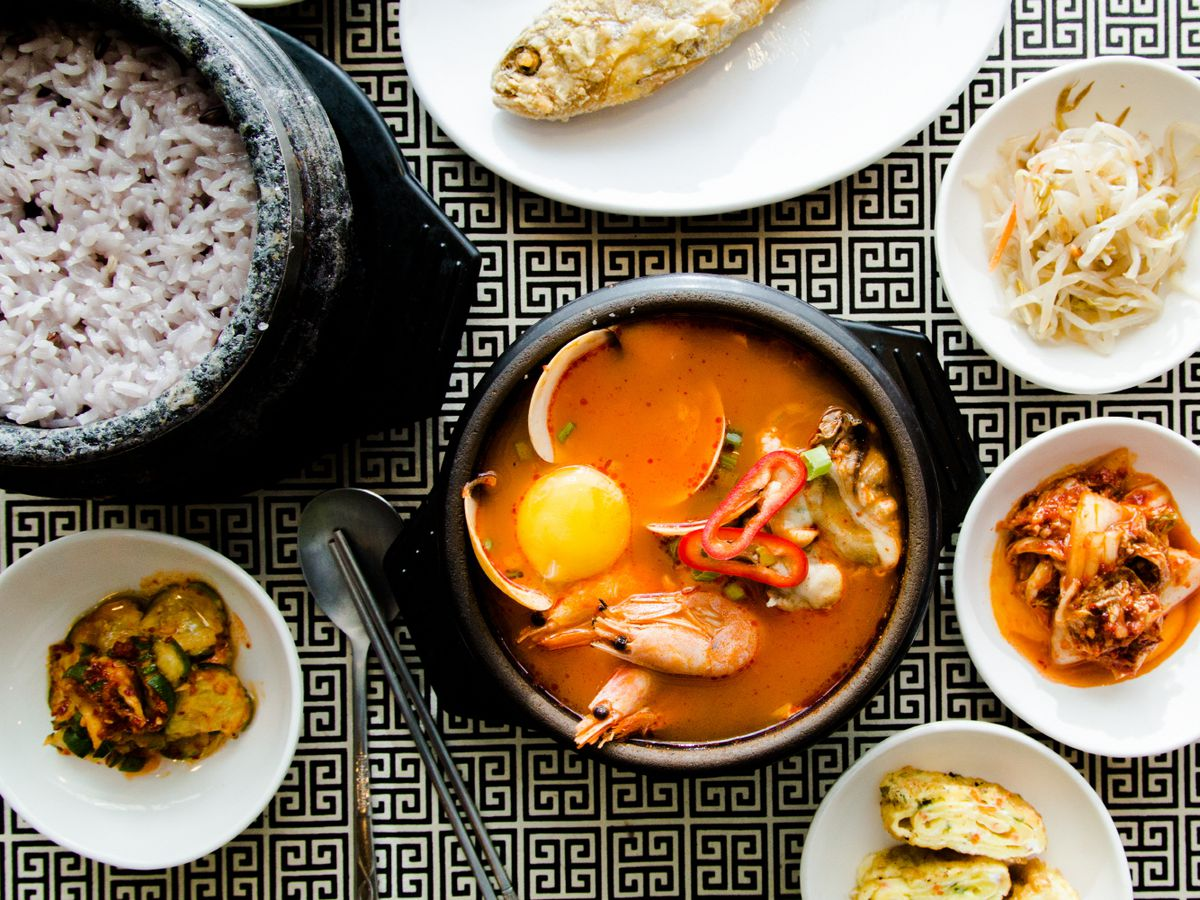 Bird's eye view of a selection of plates at Kong Tofu House, including an orange broth with prawns.