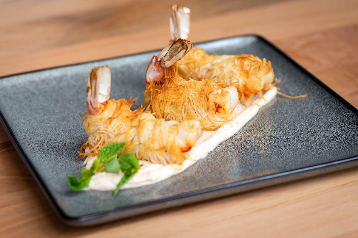 Three kataifi prawns sit on a plate.