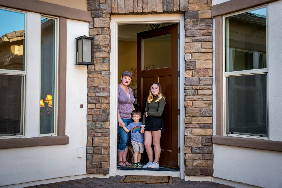 Laura Lawless and her kids, 3-year-old Connor Robertson and 11-year-old Emma Robertson, stand for a portrait at their home in Chandler, Arizona, on Wednesday, April 22, 2020. Lawless is an employment defense attorney and is working from home while taking care of her kids as a single mother during the novel coronavirus pandemic.