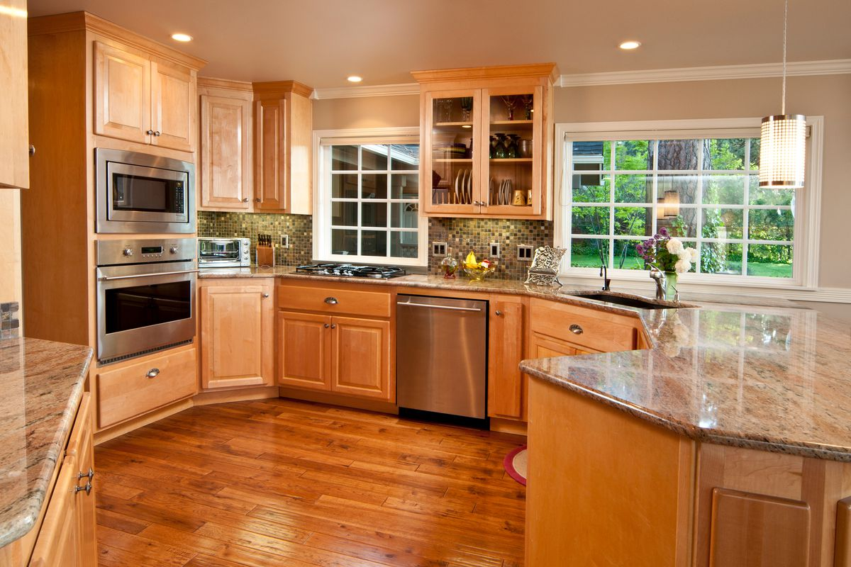 Modern, spacious kitchen with hardwood floors and cabinets.
