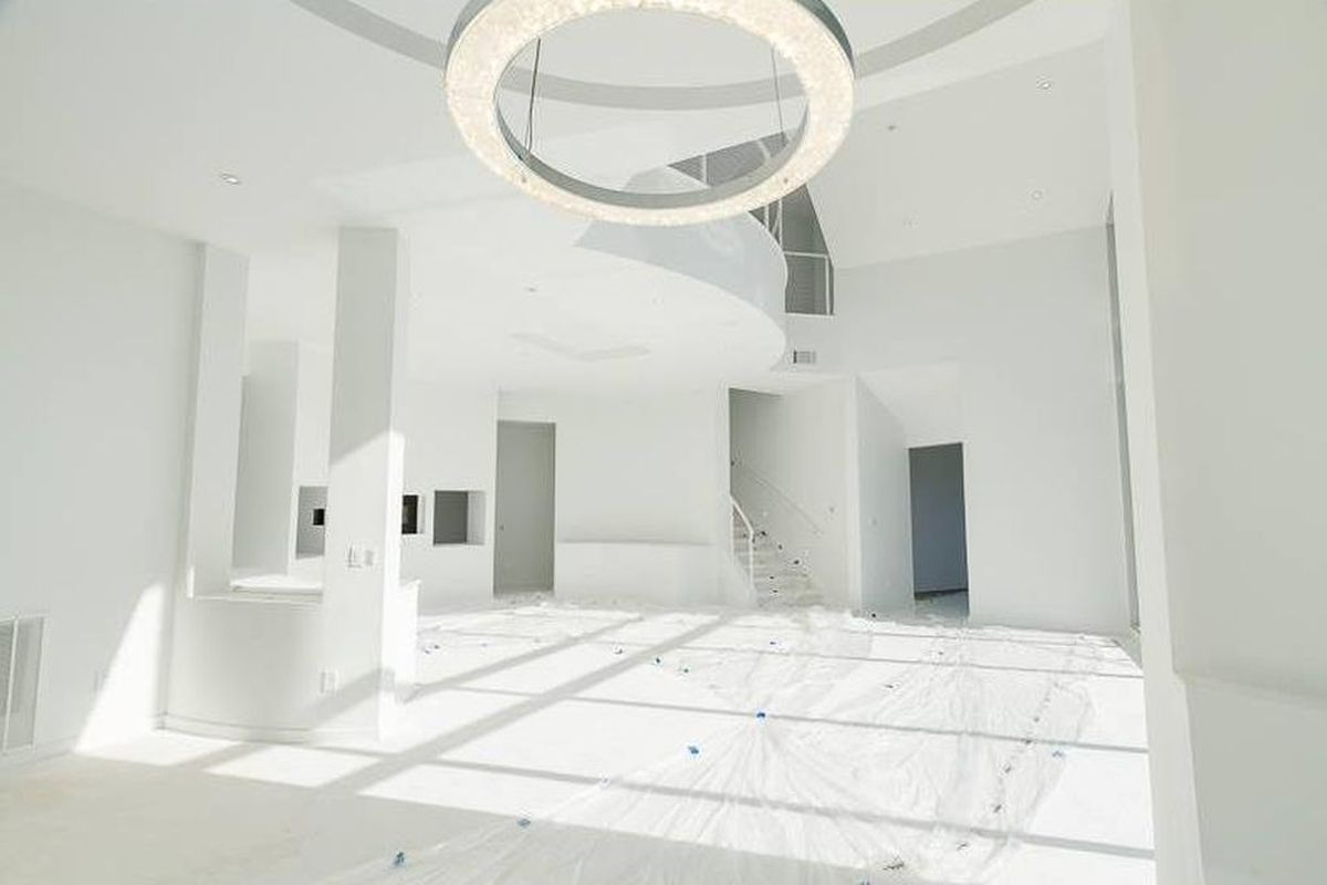 An all-white interior of a living room with two-story ceiling and round chandelier.