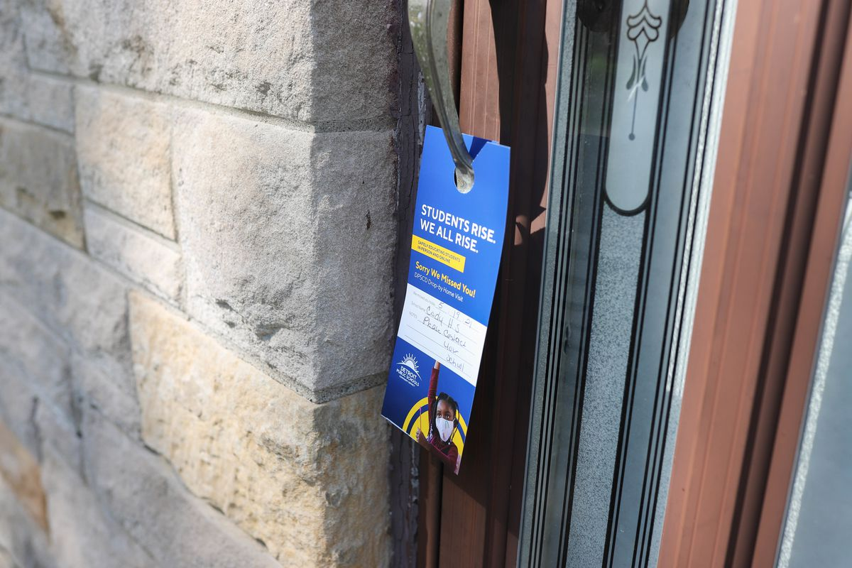 """A door placard that reads """"students rise, we all rise"""" hangs on the handle of a wooden door, left by a Detroit Public Schools' canvasser."""