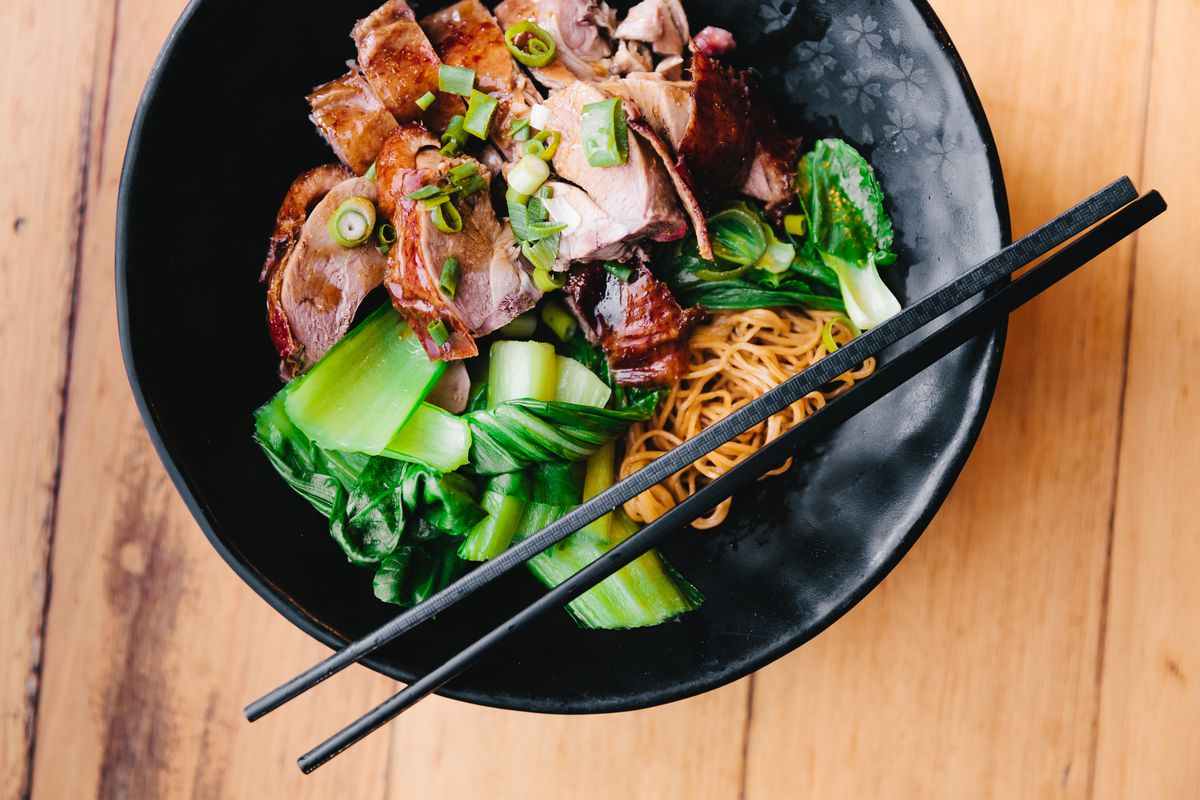 A bowl of duck alongside noodles and greens, with a set of chopsticks resting on top.