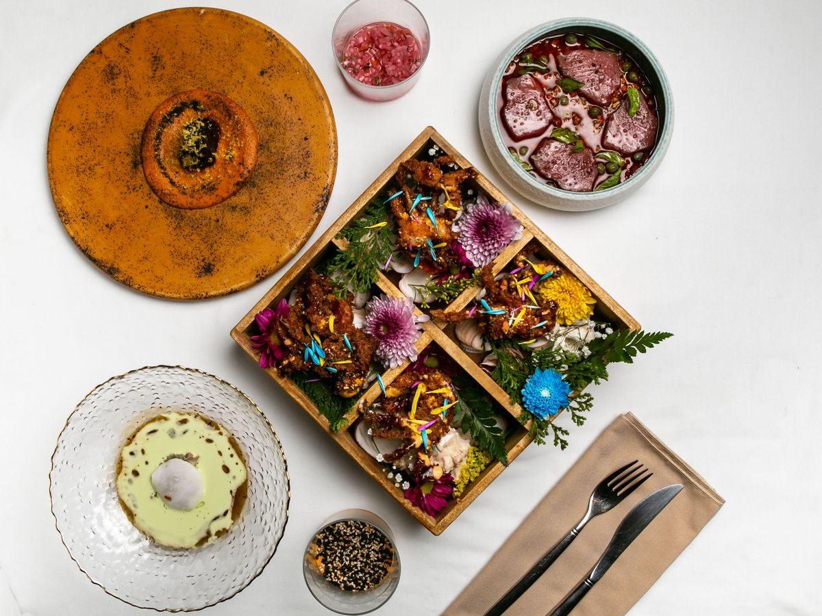 three round dishes of food sit near a square bento full of food and flowers on a tablecloth.