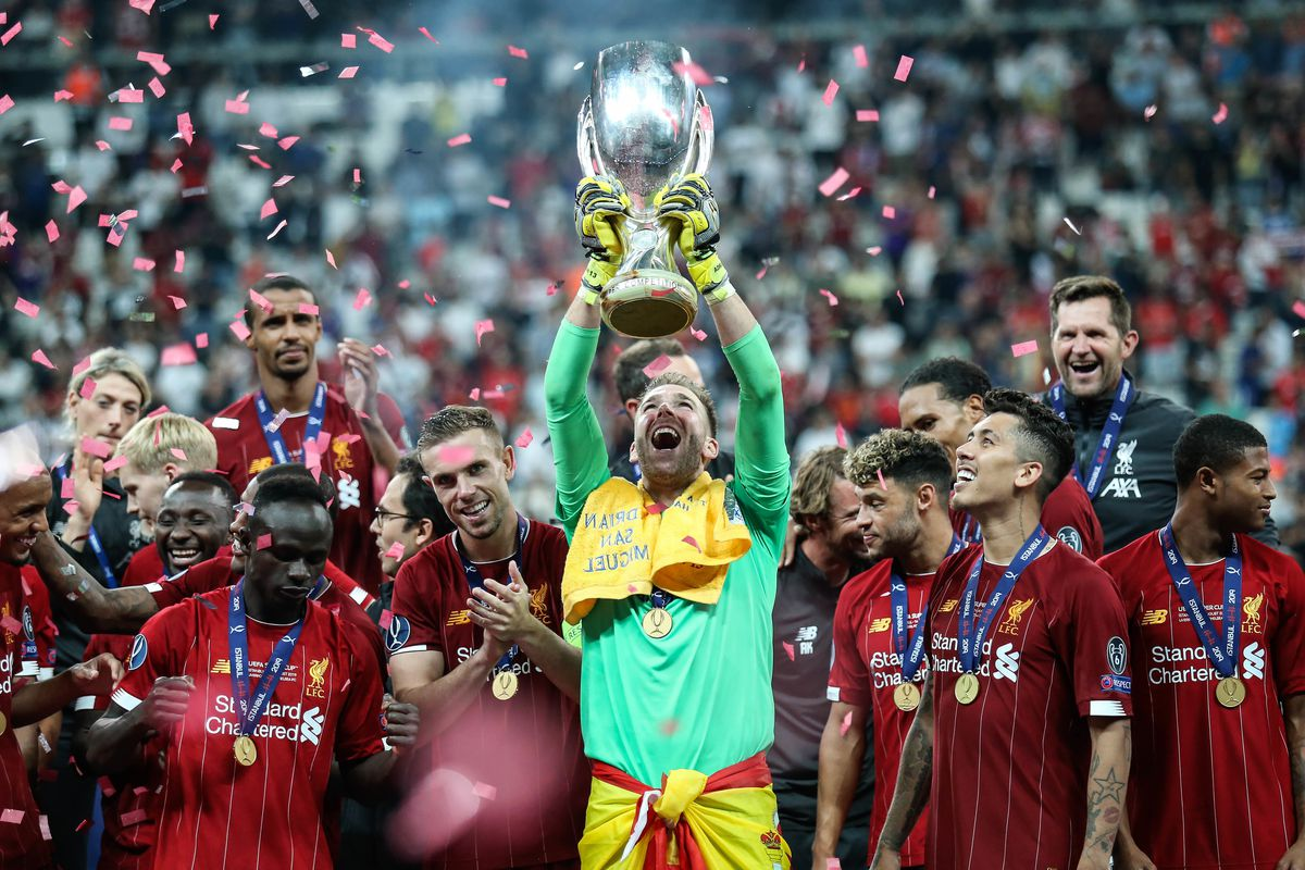 Adrian of Liverpool celebrates with the trophy and his team-...
