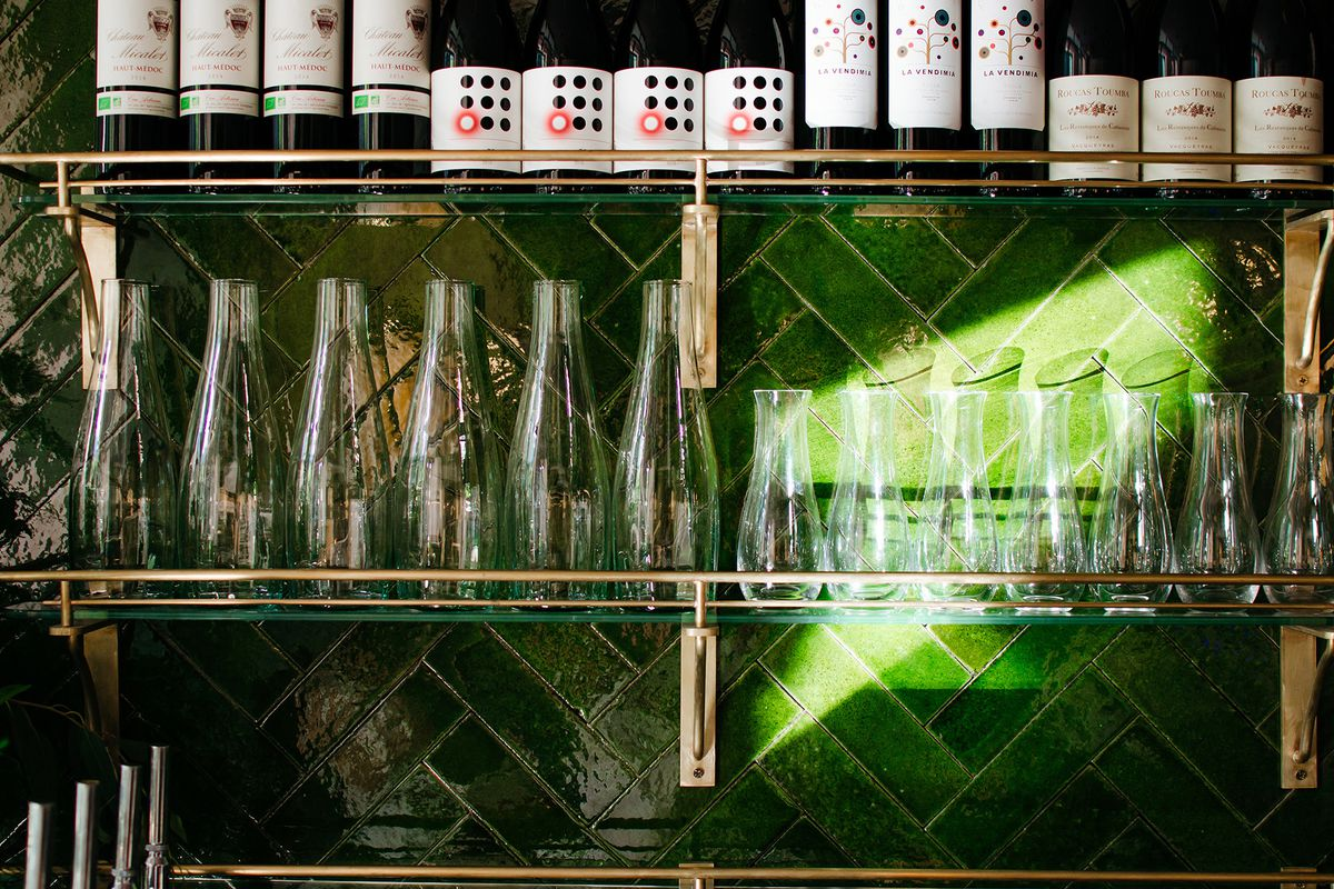 Glassware behind a green-tiled bar at Cora Pearl, a new London restaurant in Covent Garden