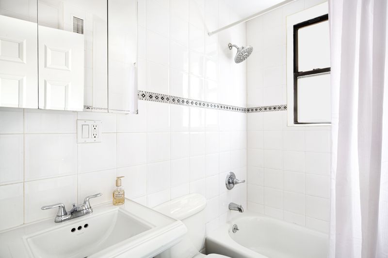 A bathroom with white wall tiles.