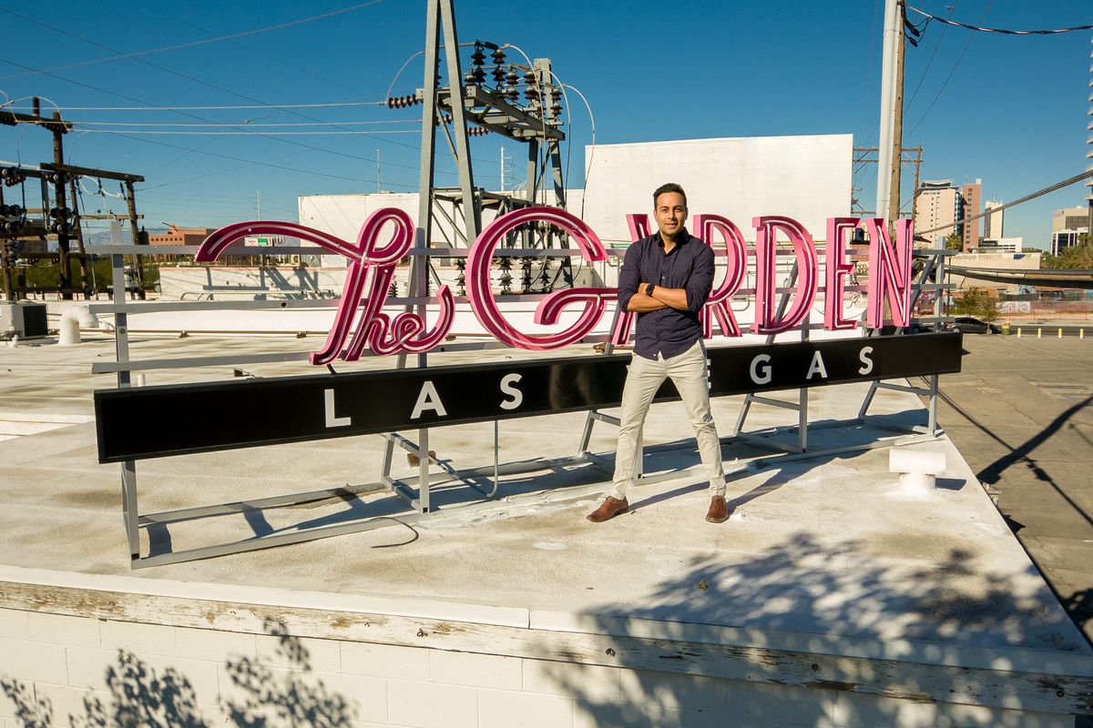 A man stands in front of a rooftop sign