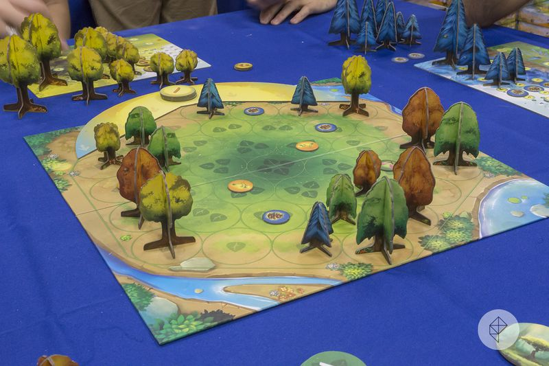 Green, yellow, brown and blue trees made of cardboard spring up around a brightly-colored forest clearing.
