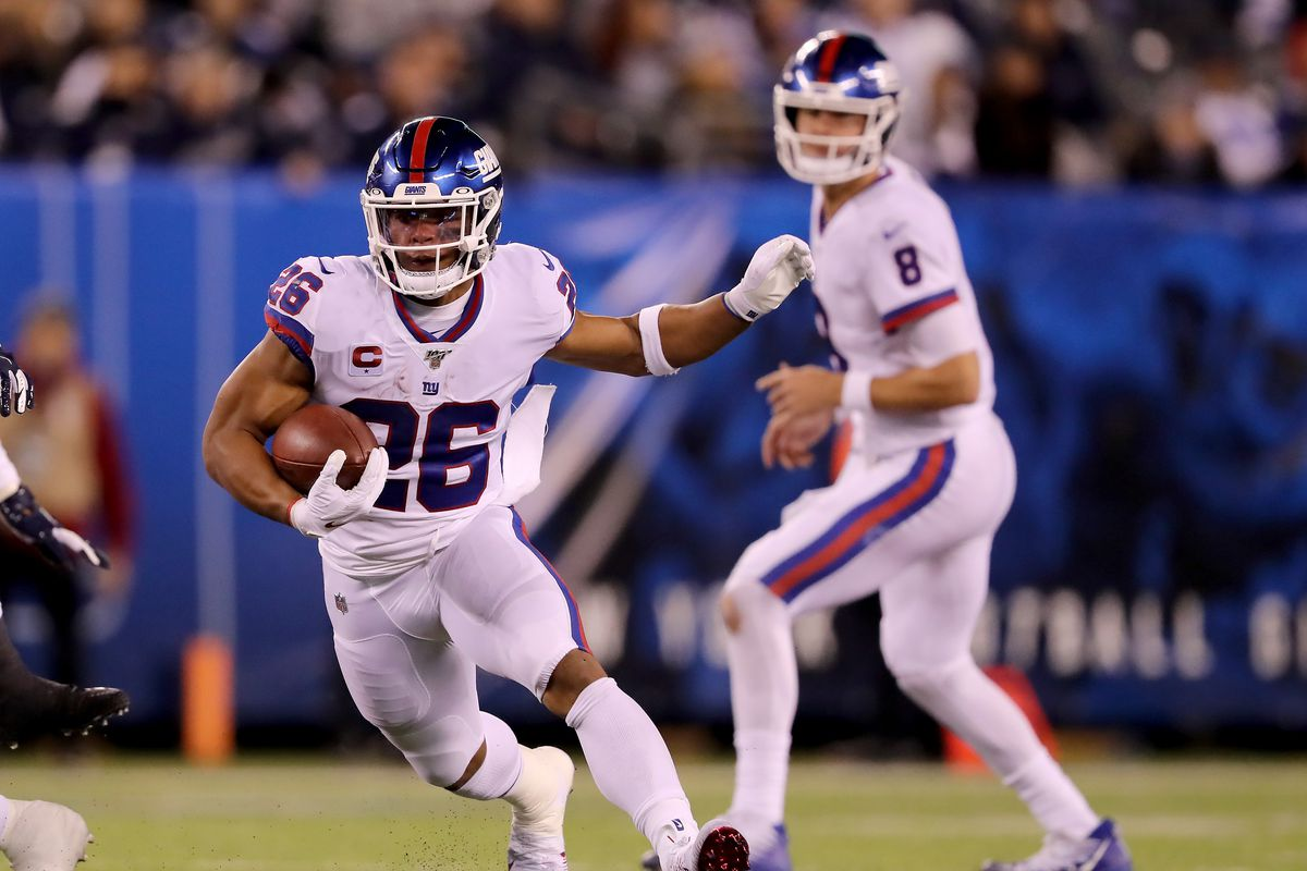 Saquon Barkley of the New York Giants carries the ball as teammate Daniel Jones looks on in the third quarter against the Dallas Cowboys at MetLife Stadium on November 04, 2019 in East Rutherford, New Jersey.