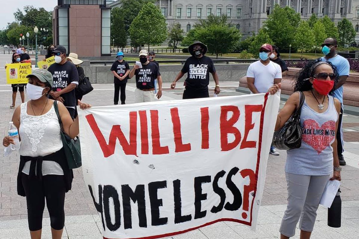 """two masked women hold a white banner with the words """"will I be homeless"""" drawn on it  in red and black paint. behind them are several people wearing black lives matter shirts and what appears to be a government building."""