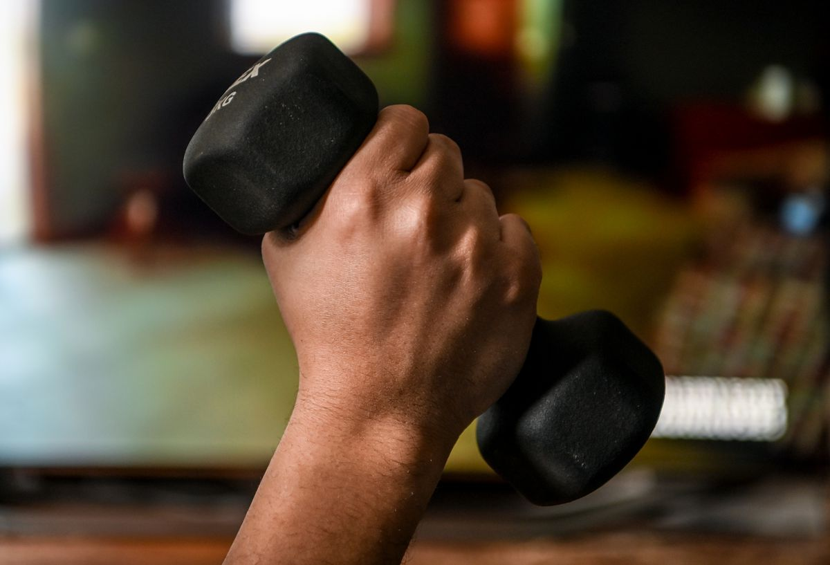 A hand holds a dumbbell in front of a television set