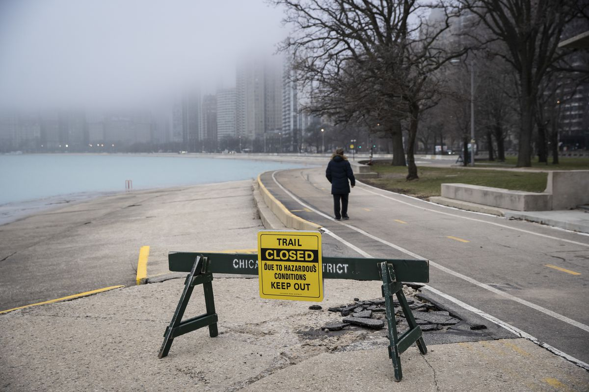 """A man ignores a """"trail closed"""" sign on the Lakefront Trail near Oak Street Beach as the city closes the area to pedestrians amid fears of the coronavirus pandemic, Thursday morning, March 26, 2020."""