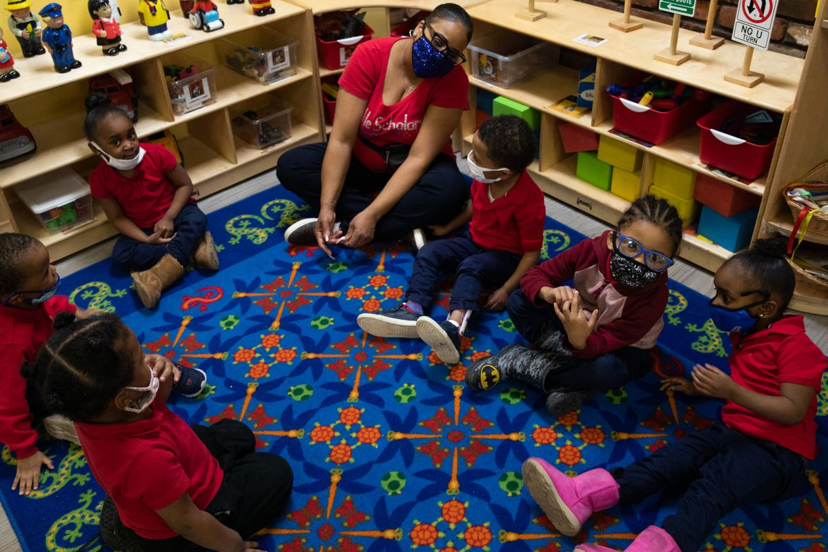 Preschoolers sit in a circle as they participate in morning exercises at Little Scholars child care center in Detroit, Michigan, U.S., on Thursday April 1, 2021.