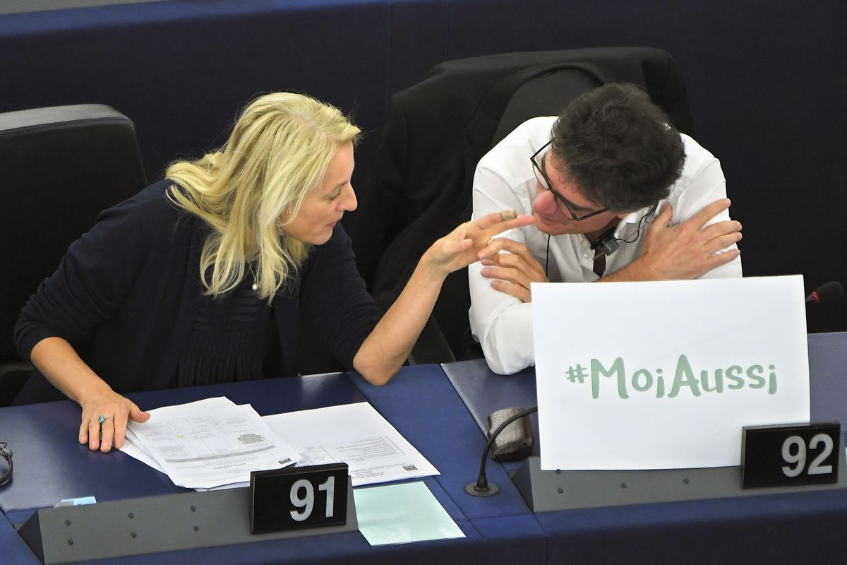 """Austrian member of the European Parliament, Evelyn Regner (left) and French member of the European Parliament Patrick Durand, talk behind a placard reading """"Me too"""", during a debate about sexual harassment and abuse on October 25, 2017."""