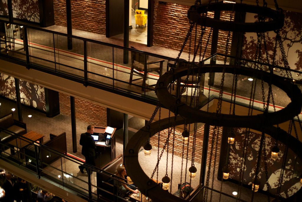 An open, very high-ceilinged hotel interior with runs of open hallways above, and there are chandeliers hanging down.